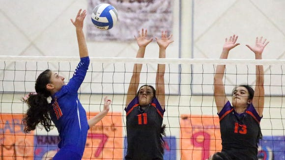 Kayla Carrillo, left, of Canutillo fires away as Zuleica Cruz, 11, and Samantha Carbojal, 13, of Eastlake rise to defend Tuesday night in Canutillo. The Eagles prevailed over the Falcons in 5 sets.