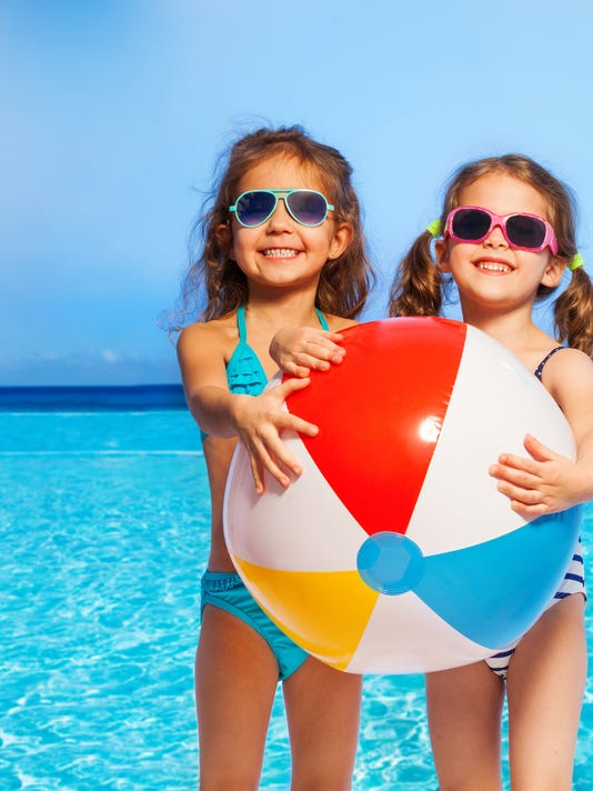 Two girls in swimwear with big inflatable ball