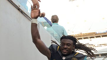Jacksonville Jaguars strong safety Johnathan Cyprien high-fives a fan after defeating the Tennessee Titans on Dec. 24, 2016, in Jacksonville, Fla.