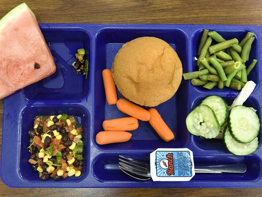 Heidi Beck, 7, surrounds her hamburger with veggies to try during an open house at Pine Meadow Elementary School in Sartell.