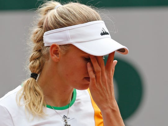 Denmark's Caroline Wozniacki wipes her face during the first round match of the French Open tennis tournament against Belgium's Yanina Wickmayer.