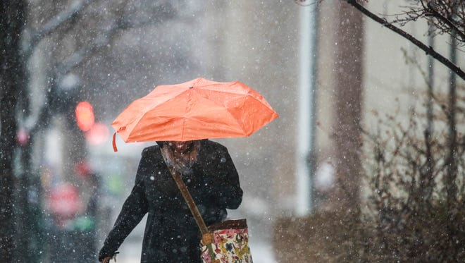 """Ebony Harris uses her orange umbrella as she makes her way to her car as Wednesday night's snow storm moves in. """"I'm sick of it,"""" Harris said. """"But, I do kind of like it. It makes me laugh."""" March 4, 2015"""