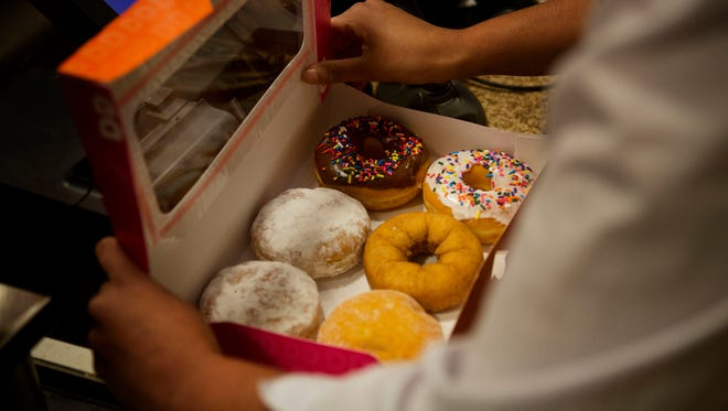 An employee fills a doughnut order for a customer at a Dunkin' Donuts in New York, U.S., on Tuesday, Feb. 24, 2014.  Photographer: Victor J. Blue/Bloomberg ORG XMIT: 539842001