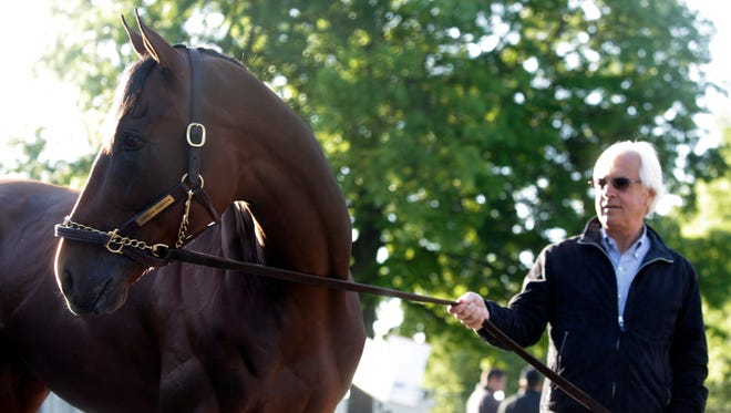Trainer Bob Baffert held Ameican Pharoah on Sunday morning, after his historic Triple Crown victory in the Belmont Stakes. June 7, 2015.