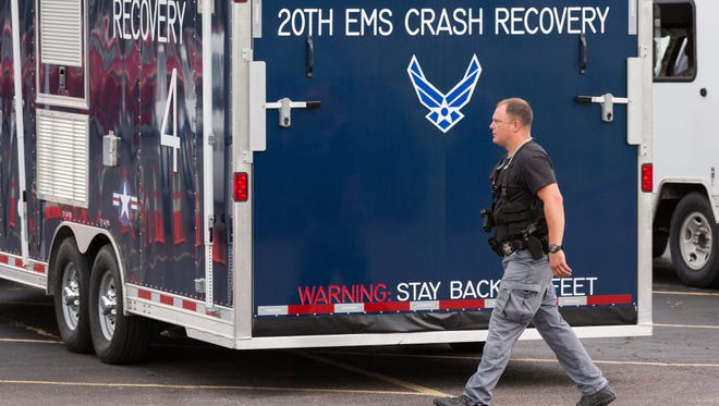 Military and civilian emergency crews gather at the command center set up near where a U.S. Air Force F-16 fighter aircraft collided with a small Cessna 150 private aircraft in Moncks Corner, S.C.
