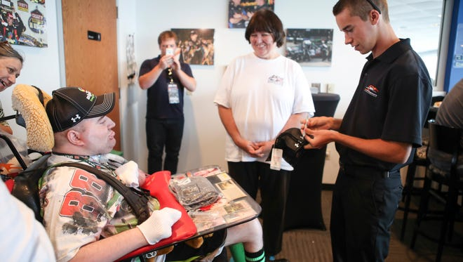 """Louisville native and NASCAR Xfinity Series driver Ben Rhodes, right, signs hats and shirts for fan Jacob Owen who was born with cerebral palsy as family friend Cathy Manion looks on. """"He goes through a lot to get here,"""" Manion said. """"He watches it all on TV and his eyes go up when he's excited. When he meets someone like this, his eyes are always up."""" For Rhodes, the experience is humbling and inspiring. """"It puts a lot in perspective in how we take our health for granted at times,"""" Rhodes said. """"It means a lot to have fans like this in NASCAR."""""""
