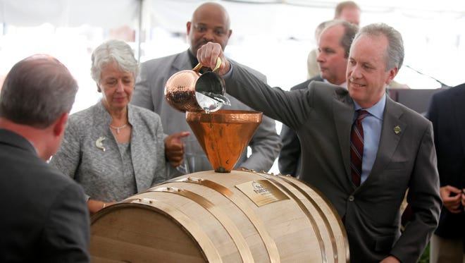 Louisville Mayor Greg Fischer poured water into a bourbon barrel as part of the groundbreaking for the new Old Forrester distiller on Main Street. July 22, 2015.