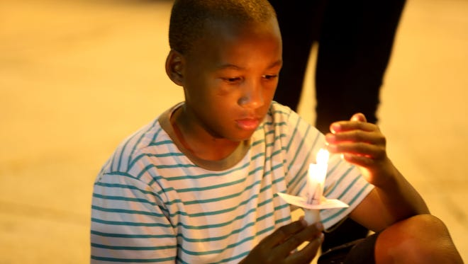 Jelani Walker, 10, holds a candle in memory of Samuel DuBose outside of the Hamilton County Courthouse Friday July 31, 2015. DuBose who was shot and killed by former University of Cincinnati police officer Ray Tensing during a traffic stop July 19 .