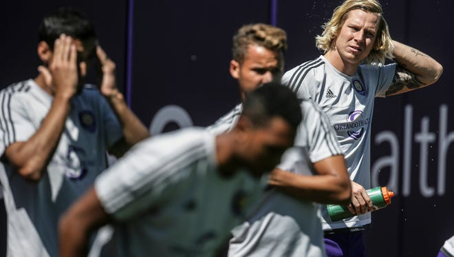 Orlando City SC star Brek Shea throws water over his head during a light practice as he returns from a sports hernia surgery. Aug. 25, 2015