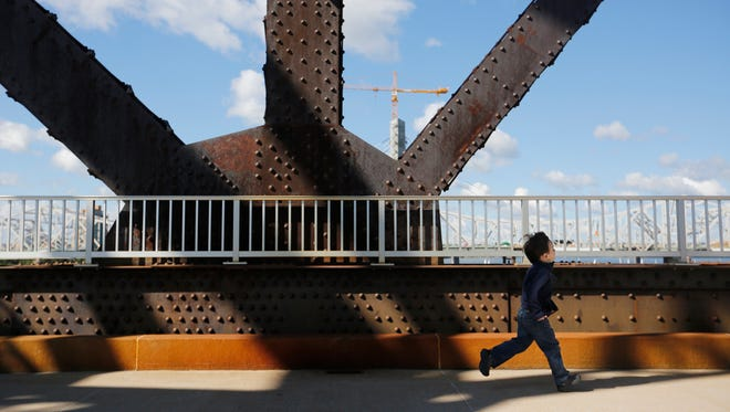 A small boy scampered under one the massive steel supports of the Big Four Bridge. Sept. 13, 2015.