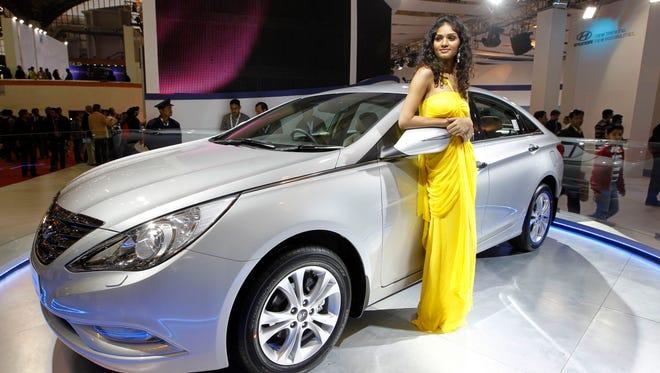 A model poses near the new version of Hyundai Sonata displayed at the Hyundai stall during Auto Expo in New Delhi, India.