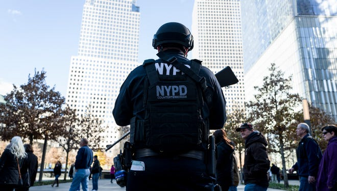 New York Police Department officer stands guard outside of the 9/11 Memorial  following a series of terrorist attacks in the French capital on November 14, 2015 in New York City. Security in New York City has increased following the  a coordinated assault on Paris which ISIS claimed responsibility for that left at least 132 people killed.