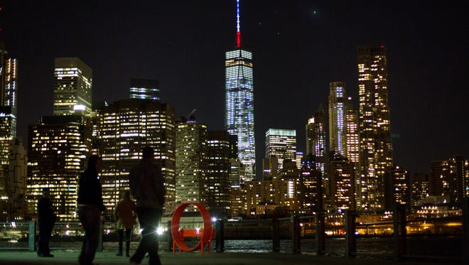 The One World Trade Center spire is lit blue, white and red after New York Gov. Andrew Cuomo announced the lighting in honor of dozens killed in the Paris attacks Friday, Nov. 13, 2015, in New York. French officials say several dozen people have been killed in shootings and explosions at a theater, restaurant and elsewhere in Paris.