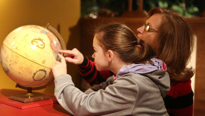 Brea Lindsey, 10, and her mother, Renee, look for a location on a map as part of an interactive exhibit on the Lewis and Clark exposition at the Frazier History Museum. Nov. 25, 2015.