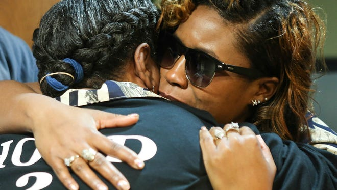 Darlene McNealy, mother of Joe McNealy who was shot and killed in 2009, hugs Kela Brasher, the mother of Steve Bledsoe, another victim to violence that was murdered in 2013. The two mothers agreed to shake hands and hug as an official peace agreement.