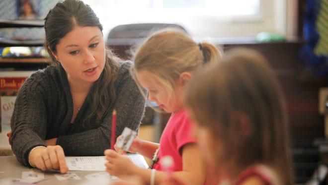 Bloom Elemenatary kindergarten instructional assistant Laura Farmer worked with children during class.  Dec. 9, 2015.