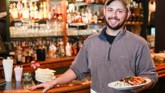 The Bristol Bar & Grille chef Austin Wilson holds the honey chipotle pork loin with cilantro rice and fajita vegetables at the Bardstown Road restaurant. The restaurant will be featuring new dishes that use the honey sourced from the beehive on the roof of the restaurant. Dec. 21, 2015