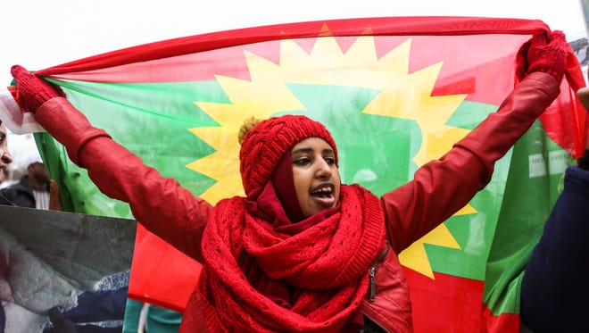 Sima Amhamed holds the Ethiopian flag as she chants along with fellow protesters outside the Federal Building on West Broadway Wednesday afternoon as they dencounce US support of the Ethiopian government. Dec. 23, 2015