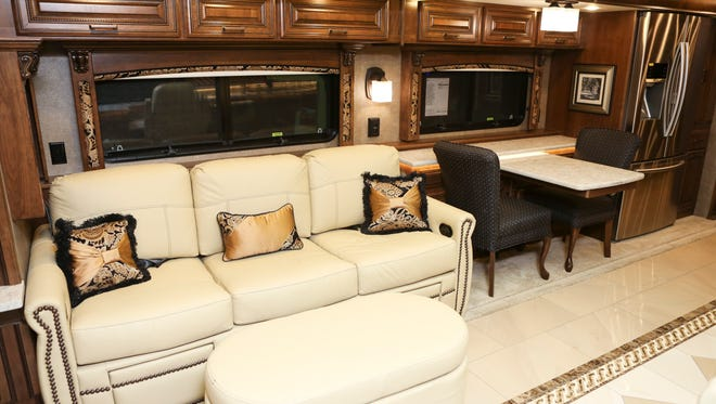 A cream-colored leather couch with foot stool and dining table in the Cornerstone Entegra RV sold by Roger Youngblood.