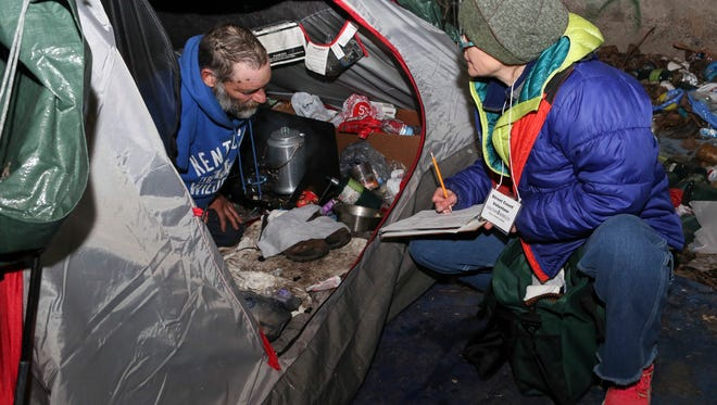 """Libbie Gonce gets information from Tony, a homeless resident in Louisville's """"Campbell Camp,"""" early Wednesday morning during the annual Homeless Count event. Jan. 27, 2016"""