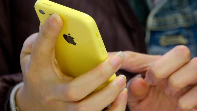 A person using an Apple iPhone 5c mobile phone.