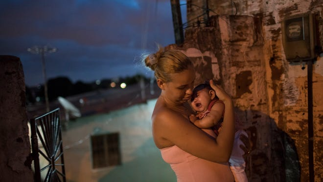 In this Wednesday, Jan. 27, 2016 file photo, Gleyse Kelly da Silva, 27, holds her daughter Maria Giovanna, who was born with microcephaly, outside their house in Recife, Pernambuco state, Brazil. Women who got pregnant during a Zika outbreak in Tahiti two years ago had about a 1 percent chance of having a baby with an abnormally small head, according to a new study published Tuesday, March 15. It's a surprisingly low risk that experts say might not match the threat of the epidemic now spreading explosively in the Americas.  The World Health Organization declared Zika to be a global emergency last month, based on suspicions it is causing a spike in a worrying birth defect known as microcephaly as well as a rare condition that sometimes results in temporary paralysis.