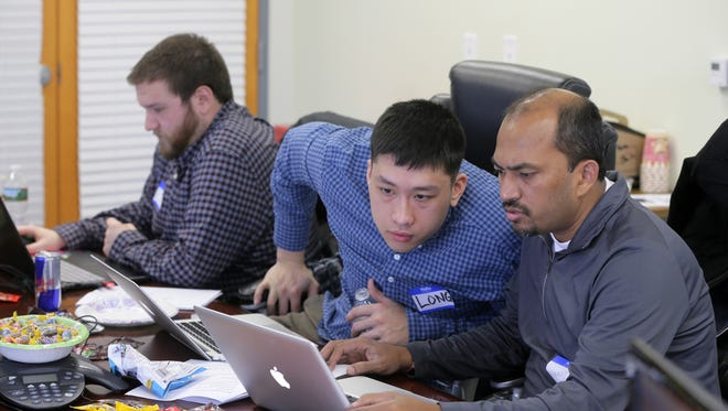 (Left to right) Rutgers Coding Bootcamp students Tammer Galal of Clinton, Long Phan of Edison and Chinmay Das of Edison participate in the Hackathon at V12 Group in Red Bank on April 8.