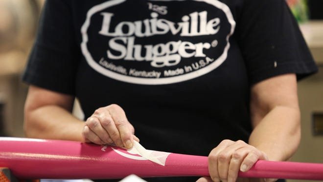 Louisville Bat Factory employee Lisa Blackman puts labels on pink bats being manufactured Wednesday for MLB players to use on Mother's Day. After the bats are used by players, they will be autographed and collected by MLB and auctioned off to raise money and awareness for breast cancer research and screenings. April 27, 2016