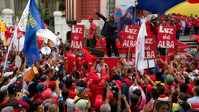 Venezuela's President Nicolas Maduro speaks to supporters during a May Day march in Caracas, Venezuela, Sunday. President Maduro ordered a 30 percent increase in the minimum wage, the latest move by the socialist government to grapple with high inflation and economic stagnation.