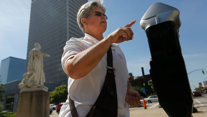Kathy Kesinger paid to park at a meter on Sixth Street, in downtown Louisville. Parking rates for meters and city garages will be increasing as of Friday, July 1.