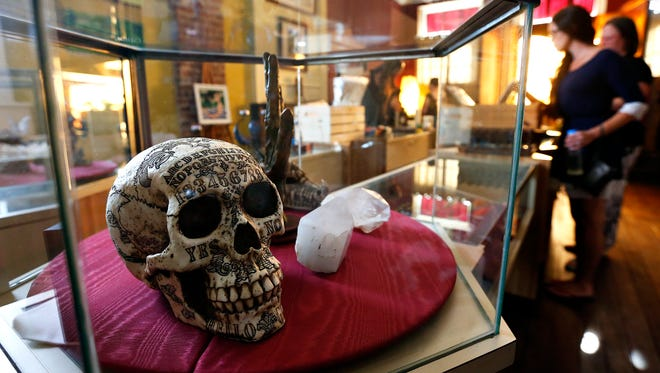 A novelty skull sits in a display case along with other esoteric items during the grand opening of The Alchemist's Attic in downtown Springfield, Mo. on July 1, 2016.