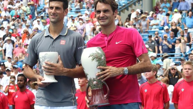 Novak Djokovic, left, and Roger Federer show their Rookwood Pottery trophies after the Western & Southern Open finals at the Lindner Family Tennis Center in Mason on Aug. 23, 2015. Federer won 7-6 (1), 6-3.