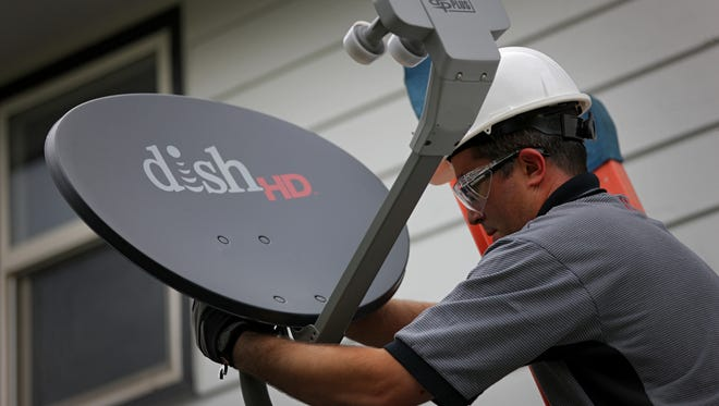 Justin Preziosi, field service specialist for Dish Network Corp., installs a satellite television system at a residence in Denver, Colorado, U.S., on Tuesday, Aug. 6, 2013.
