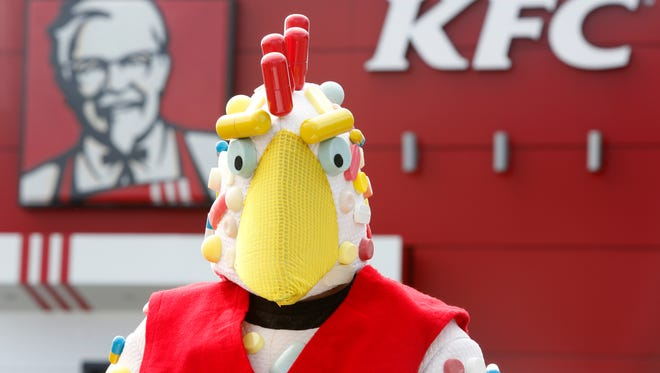A man in a pill covered chicken suit joined other protesters at a KFC restaurant on Bardstown Rd., calling for the end of the use of antibiotics in the company's chicken. Aug. 10, 2016.