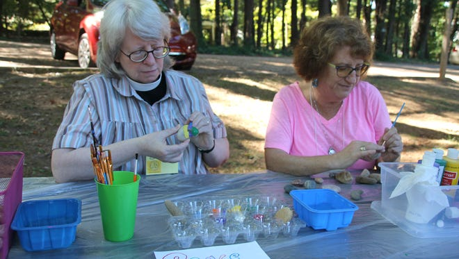 Beth Darling, priest at St. George Episcopal Church, and Deb Cox, a church member, paint peace rocks in celebration of Peace Day on Sept. 24. Peace Day is celebrated around the world on Sept. 21 each year.