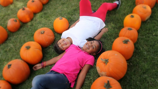 Kennedi Brown and Kiannalise Perez, best friends from North Elementary, take a break in the Grace United Methodist Pumpkin Patch after searching for the perfect pumpkin to take home.