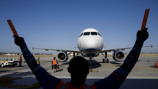 An aircraft marshaller guides a JetBlue plane on the tarmac at Long Beach Airport in Long Beach, California, on April 25. The U.S. Department of Transportation will be requiring performance information on flights operated by a half dozen regional airlines.
