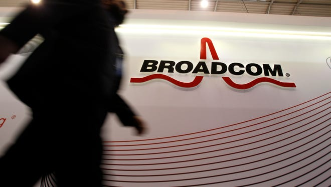 An attendee passes the Broadcom Corp. pavilon on day two of the Mobile World Congress in Barcelona, Spain, on Tuesday, Feb. 25, 2014.