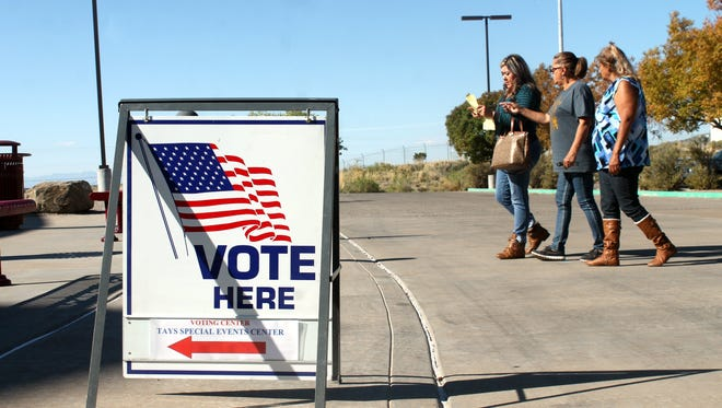 In this file photo, residents look over their sample ballot before entering the Tays Center.