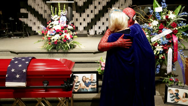 Damon Cole, of the Fort Worth Police Department, dressed as Spider-Man, hugs Christina Wascher, of Miami, dressed as a Disney princess, during a funeral service for Damian Creed, who died of cancer at the age of 4, at New Hope Ministries in East Naples on Thursday, Nov. 10, 2016. The service was attended by first responders from Lee and Collier counties. The family suggested that attendees wear their favorite superhero costume to honor Creed.
