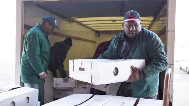 Volunteers Thomas McDonald, left, and Perch Edwards help unload frozen turkeys from a Kentucky Harvest truck with volunteers from the LMPD Narcotics Divisionat the Plymouth Community Renewal Center. Nov. 21, 2016