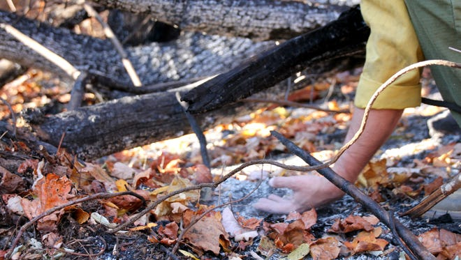 A firefighter runs his hand over smoldering leaves to check for hot spots Nov. 26 at the Party Rock fire near Lake Lure. Crews checked to make sure no new fire starts could occur along the 7,171 acres the fire has spread. It was 80 percent contained Saturday.