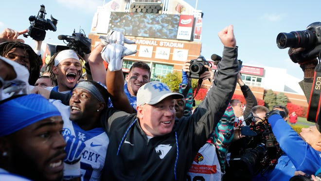 Kentucky coach Mark Stoops celebrates with his team after defeating Louisville 41-38. Nov. 26, 2016