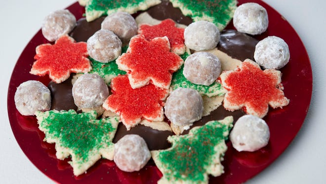 A platter of amaretti cookies, mocha butter balls and coconut cookie cutouts.
