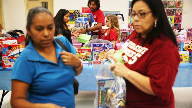 Volunteers help parents pick out toys for their children during the Holiday Gift Shop at the Guadalupe Center in Immokalee on Wednesday, Dec. 14, 2016. Parents could pick out up to three gifts for free per child for Christmas.