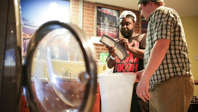 """TAYLRD peer support staff member David Murphy, right, helps member Jonta Williams with his laundry. Williams, 22, has been coming since the center opened in December 2015. """"I come here and I get a lot of positive vibes from being around a lot of really dedicated caseworkers,"""" Williams said. Being homeless in Louisville was difficult for Williams and he is hoping to have his own place soon. """"This helps me look forward to the future and becoming a productive adult."""""""
