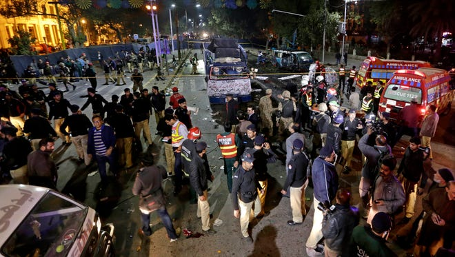 Security officials inspect the scene of a suicide bomb attack that targeted a protest by pharmacists in Lahore, Pakistan, on Feb. 13, 2017.
