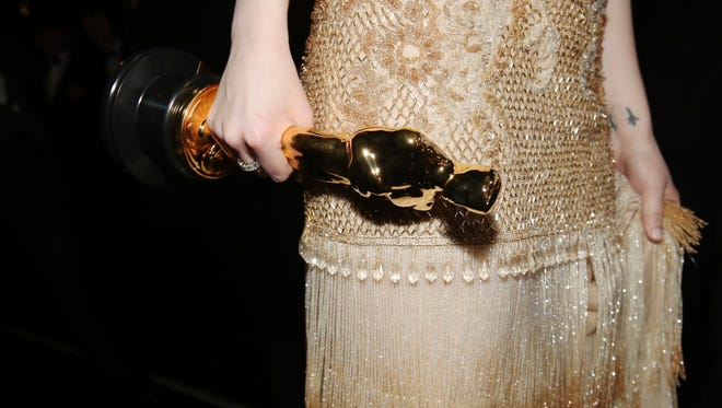 Emma Stone carries her Oscar backstage during the Academy Awards on Feb. 26, 2017, in Hollywood, Calif.