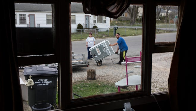 """Carla King, left, helps Michael Parrish load up a washer on to his trailer as he packs his family's belongings out of their Pleasant Ridge home. The family had to be out by March 31st, but is moving just a couple blocks away in the neighborhood where they've been told they can stay until the end of the year. """"You can't find nothing,"""" Parrish said. He looked as far as Corydon in his searches. """"They all want three times the rent and you can't do that on a fixed income."""" The family will be renting for $600-a-month at their new location, plus utilities, but only get $740-a-month from disability. March 24, 2017"""