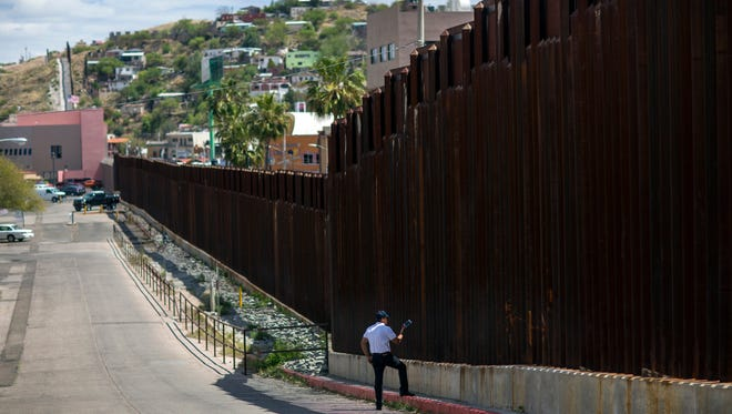 In this April 1, 2017, photo, a man in Nogales, Ariz., talks to his daughter and her mother who are standing on the other side of the border fence in Nogales, Mexico. Homeland Security Secretary John Kelly says arrests of people entering the United States illegally across the Mexican border plummeted in March 2017. That's a signal that fewer people are trying to sneak into the U.S. (AP Photo/Rodrigo Abd)